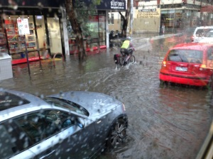 A cyclist pushes through floodwaters in Brunswick